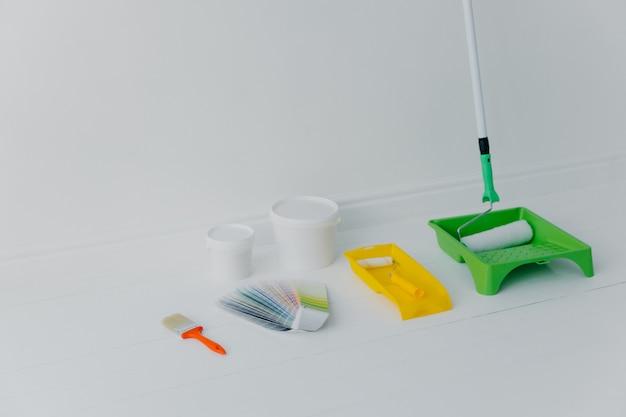 Rolo de pintura na bandeja, pincel e amostra de cor isolado sobre o branco Foto Premium