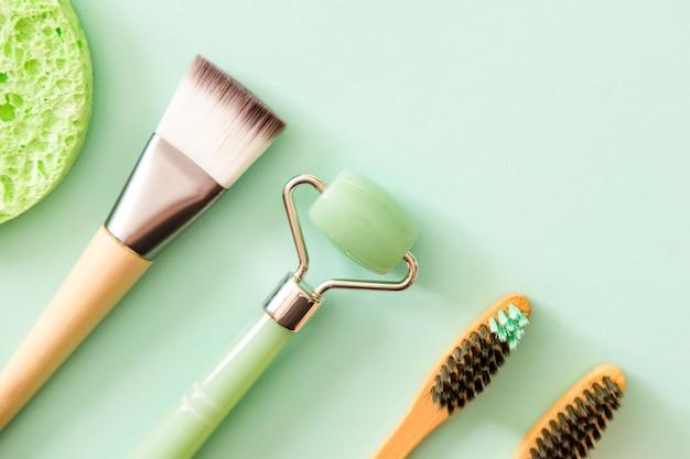 Rolo de rosto de jade verde, pincel de maquiagem, escovas de dentes de bambu naturais e esponjas. estilo liso leigo. conceito moderno de beleza de auto-cuidado. Foto Premium