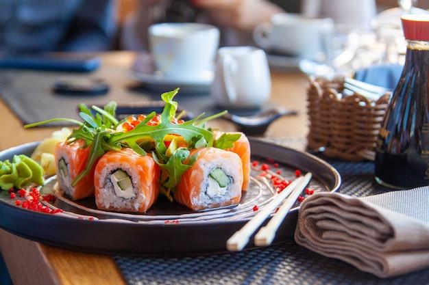 Rolo de sushi comida japonesa no restaurante. califórnia sushi roll conjunto com salmão, legumes Foto Premium