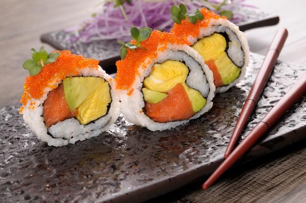 Rolo de sushi de califórnia com pauzinhos Foto gratuita