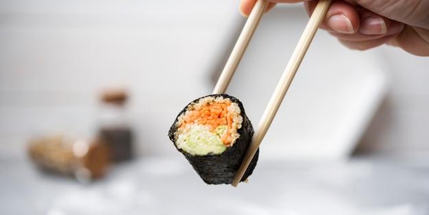 Rolo de sushi de close-up com legumes realizada em pauzinhos Foto gratuita
