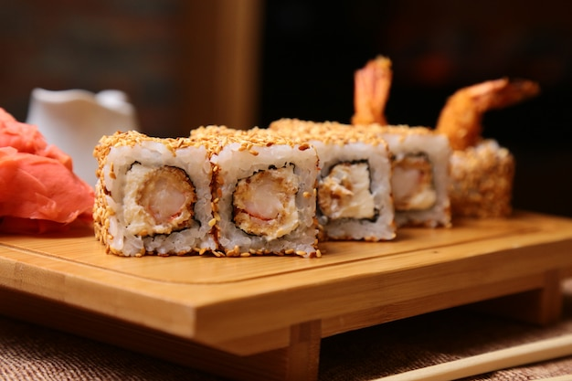 Rolo de sushi de cozinha tradicional japonesa com arroz, camarão e cream cheese e gergelim em uma placa de madeira Foto gratuita