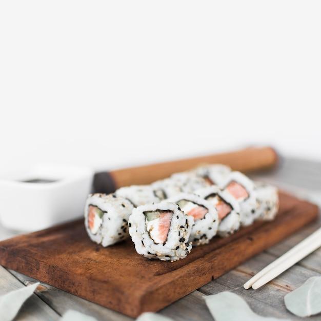 Rolo de sushi delicioso com sementes de gergelim, dispostas na bandeja de madeira Foto gratuita