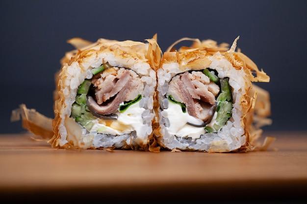 Rolo de sushi japonês com salmão e pepino no escuro Foto Premium