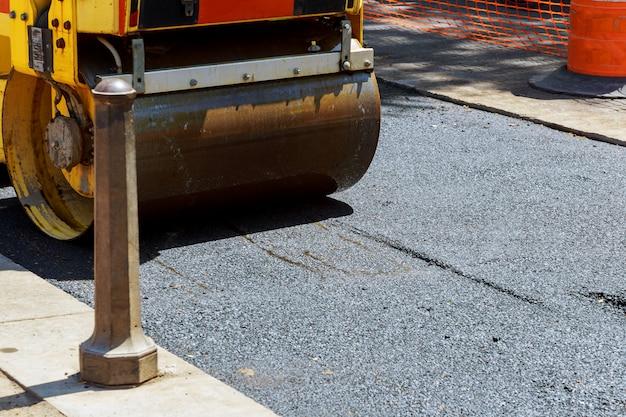 Rolo e trabalhadores na asfaltagem e reparação de ruas da cidade Foto Premium