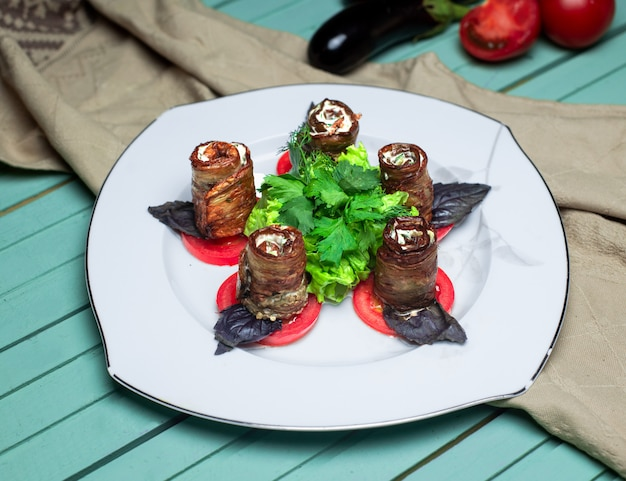 Rolos de berinjela com salada de legumes no prato branco. Foto gratuita