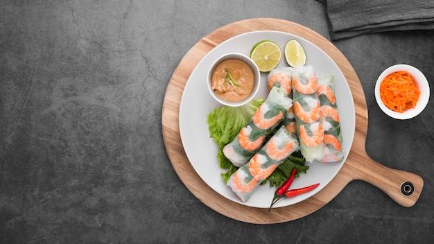 Rolos de camarão com molho no prato com espaço de cópia Foto gratuita