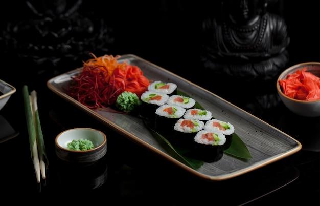 Rolos de sushi com aperitivos em um prato cinza Foto gratuita