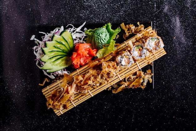 Rolos de sushi com batatas fritas e aperitivos em uma esteira de sushi. Foto gratuita