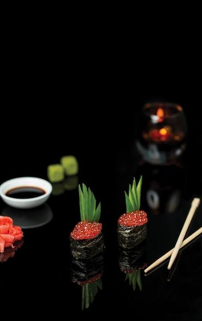Rolos de sushi com caviar de salmão e molho. Foto gratuita