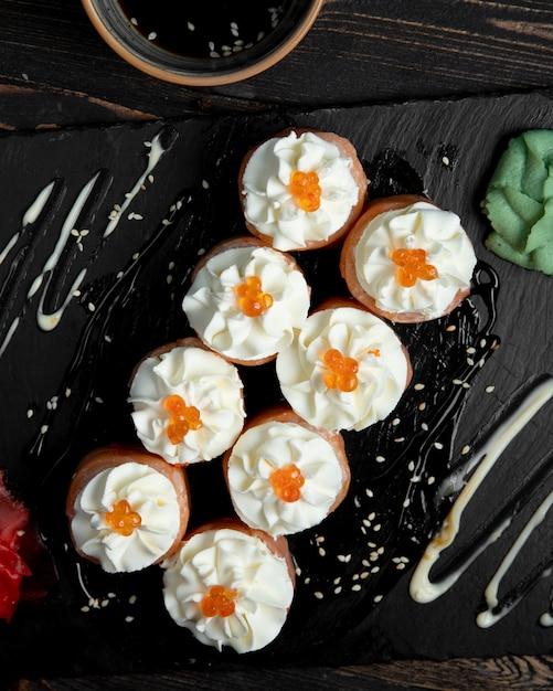 Rolos de sushi com creme e caviar vermelho servido com gengibre e wasabi Foto gratuita