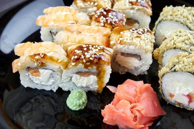 Rolos de sushi com gengibre e wasabi em uma placa preta Foto Premium
