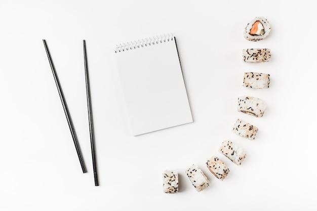 Rolos de sushi com pauzinhos e bloco de notas em espiral no fundo branco Foto gratuita