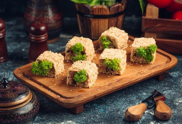Rolos de sushi com pistache verde em uma placa de madeira. Foto gratuita