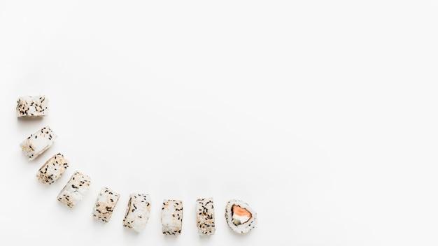 Rolos de sushi com sementes de gergelim, isoladas no fundo branco Foto gratuita