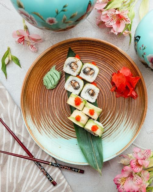 Rolos de sushi dentro da placa de design marrom azul. Foto gratuita