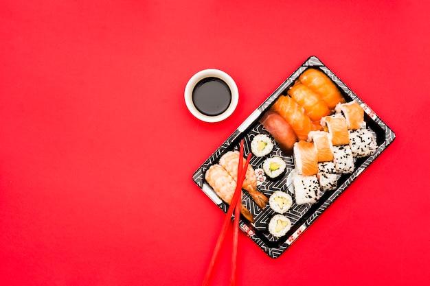 Rolos de sushi e sashimi na bandeja com molho de soja sobre fundo colorido Foto gratuita