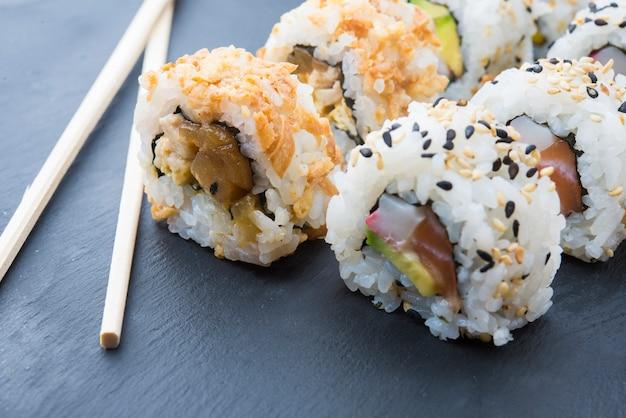 Rolos de sushi em um prato de ardósia Foto Premium