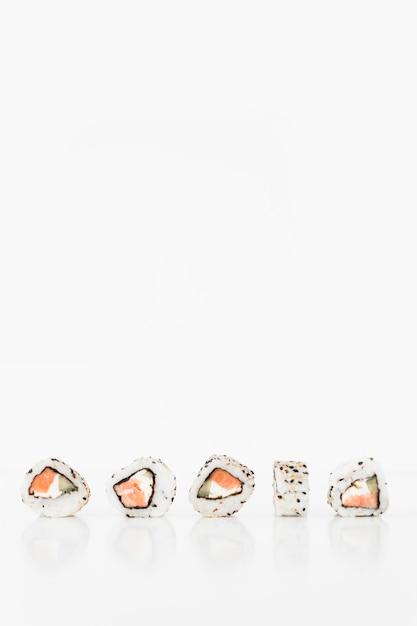 Rolos de sushi japonês fresco tradicional em um fundo branco Foto gratuita