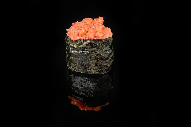 Rolos de sushi japonês fresco tradicional em um fundo preto Foto Premium
