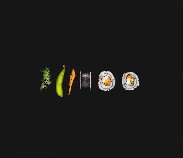 Rolos de sushi maki com edamame em fundo preto Foto gratuita