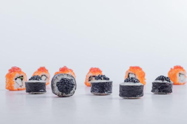 Rolos de sushi maki e califórnia em fundo branco. Foto gratuita