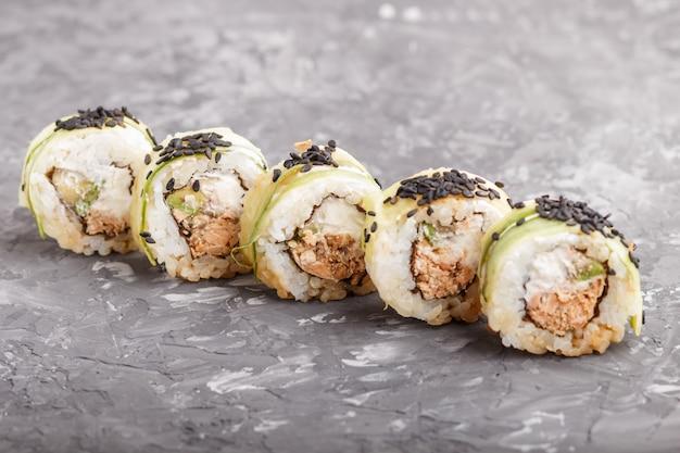 Rolos de sushi maki japonês com queijo de gergelim preto de pepino de atum em fundo preto de concreto Foto Premium