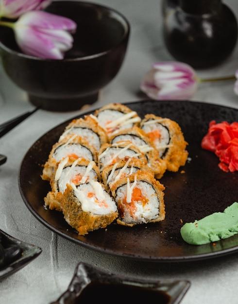 Rolos de sushi no prato blac com tulipas ao redor. Foto gratuita