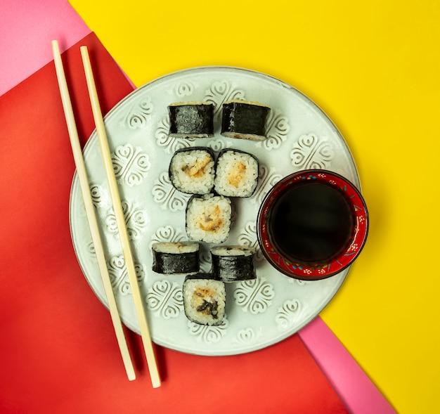 Rolos de sushi nori com enguia servidos com molho de soja Foto gratuita