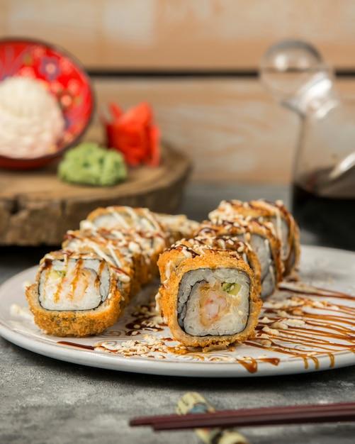 Rolos de sushi quente com camarão e pepino, guarnecidos com molho e gergelim Foto gratuita