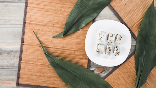 Rolos de sushi saboroso tradicional em chapa branca com placemat e folhas na mesa de madeira Foto gratuita