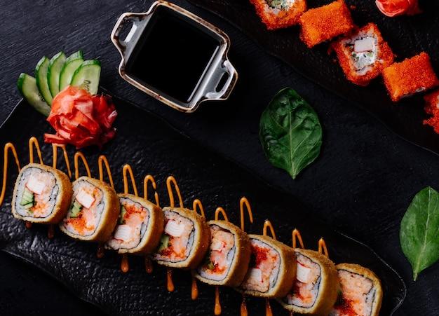 Rolos de sushi variedades em chapa preta com molho de soja. Foto gratuita