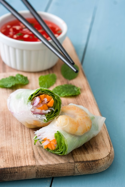 Rolos vietnamitas com legumes, macarrão de arroz e camarão na superfície de madeira azul Foto Premium