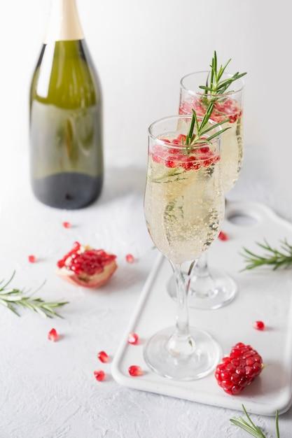 Romã cocktail com alecrim, champanhe, refrigerante na mesa cinza. bebida de férias de natal. Foto Premium