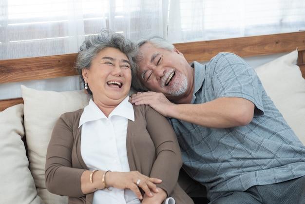 Romântico com um grande sorriso e rindo da avó asiática mais velha e avô, sente-se no sofá do sofá em casa, estilo de vida mais velho de aposentadoria Foto Premium