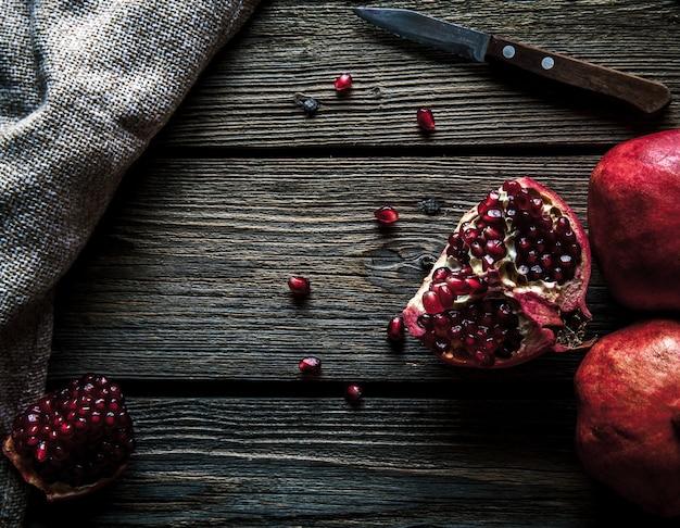 Romãs frescas em uma mesa de madeira. orgânicos, frutas, alimentos Foto Premium