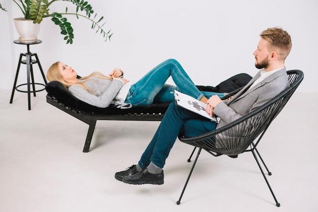 Rorschach de teste de borrão de diagnóstico psicólogo com deprimido jovem paciente deitado no sofá Foto gratuita