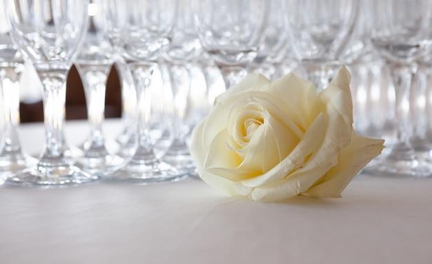 Rosa branca em cima da mesa, no fundo copos de champanhe, evento de casamento Foto Premium