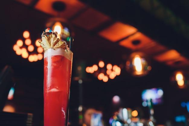 Rosa e vermelho cocktail alcoólico exótico colorido fresco com limão e gelo no bar. Foto Premium
