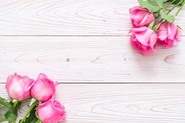 Rosa rosa em um vaso no fundo de madeira Foto Premium