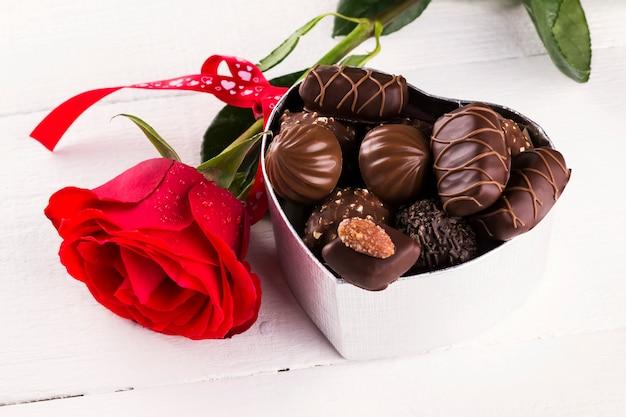 Rosa vermelha, caixa de chocolates em um fundo branco de madeira Foto Premium