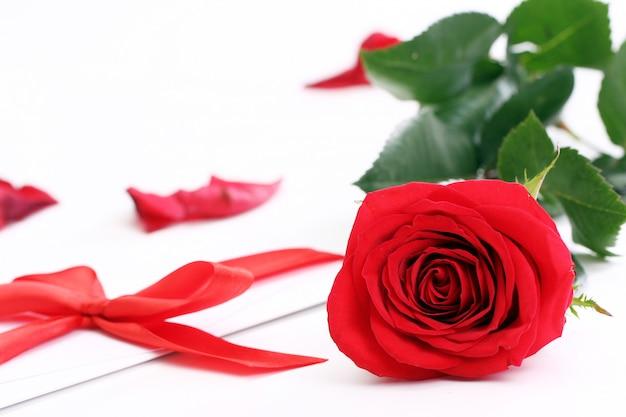 Rosa vermelha e envelope de férias Foto gratuita