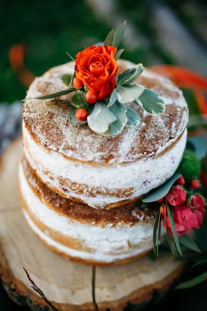 Rosa vermelha e folhas verdes colocam o saboroso bolo esponjoso Foto gratuita