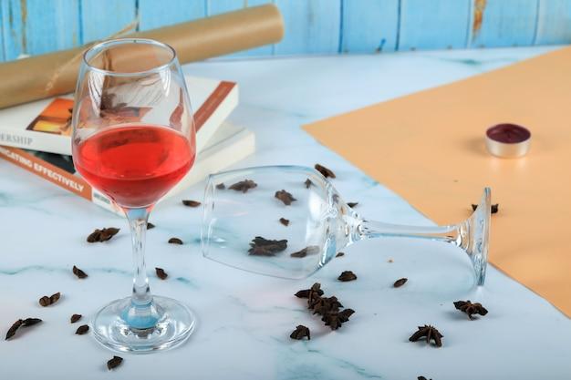 Rosa vermelha em um copo e um copo de vinho vazio no cartão Foto gratuita