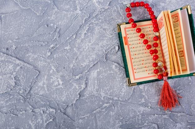 Rosário vermelho brilhante em um kuran sagrado aberto sobre o pano de fundo texturizado concreto Foto gratuita