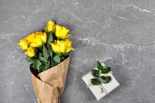 Rosas amarelas em papel artesanal e caixa para presente da moda em papel reciclado na cor cinza Foto Premium
