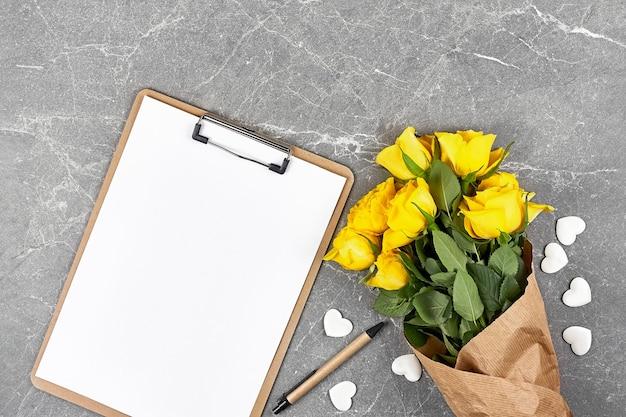 Rosas amarelas em papel artesanal e pasta de prancheta em cinza Foto Premium