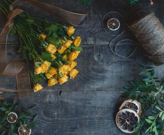 Rosas amarelas em uma mesa de madeira escura com fatias de laranja secas. Foto gratuita