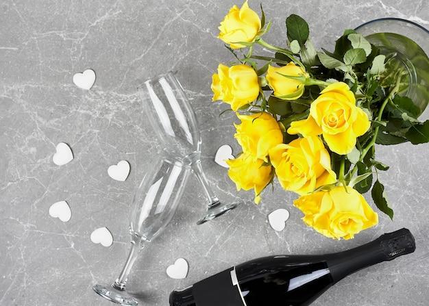 Rosas amarelas, garrafa de espumante, taça de champanhe e corações brancos em cinza Foto Premium