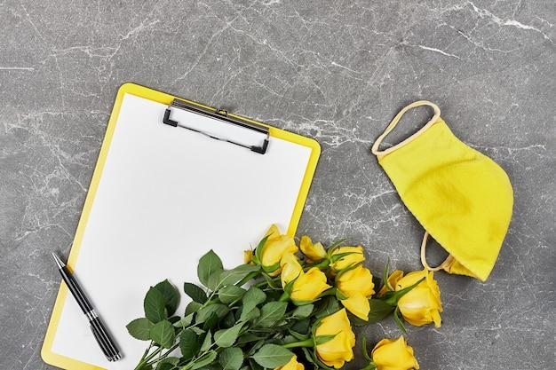 Rosas amarelas, máscara protetora amarela e pasta de prancheta em cinza Foto Premium